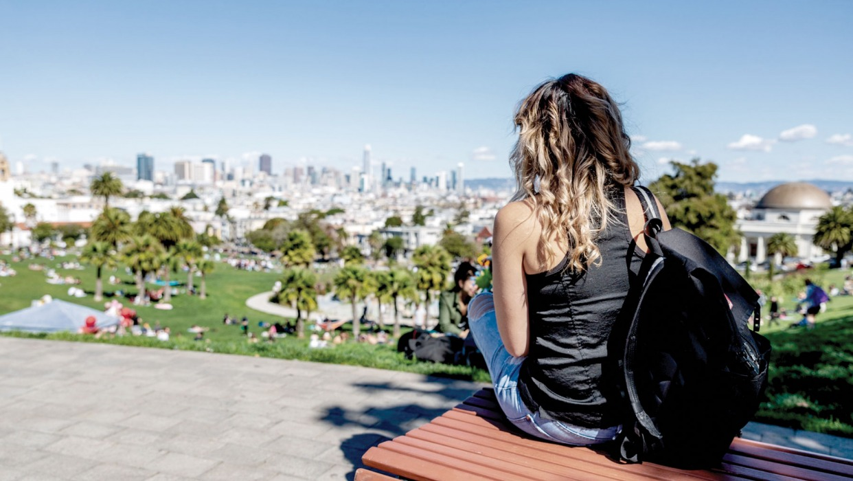 Girl looks at the San Francisco skyline from Dolores Park